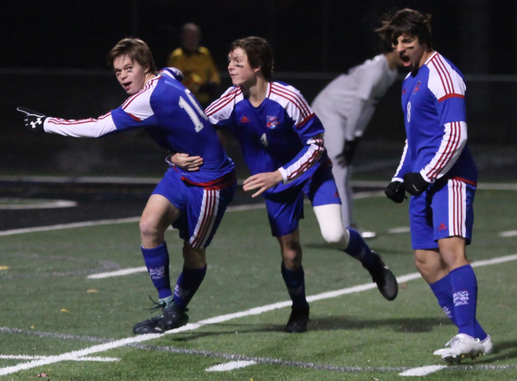 . Randy Meyers - The Morning Journal<br> Bay\'s Kyle Cusimano scored the first goal against Aurora and he is mobbed by Sam Shank and Noah Beck during the second half on Nov. 8.