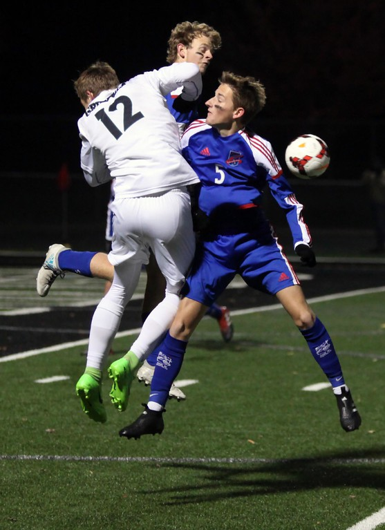 . Randy Meyers - The Morning Journal<br> Aurora\'s Cade Huffman goes up between Ben Humphrey and Jack Graham of Bay to deflect the ball during the first half of the state semifinal on Nov. 8.