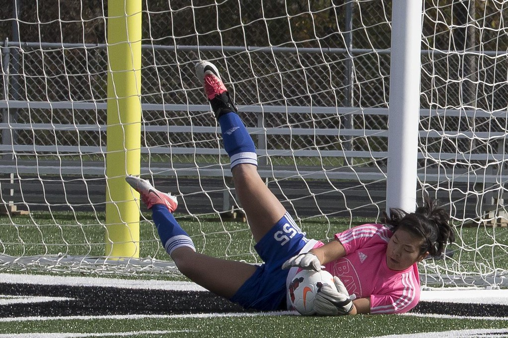 . Jen Forbus - The Morning Journal<br> Bay goalie Gigi Merk makes a diving save against Madison Comprehensive on Nov. 4.