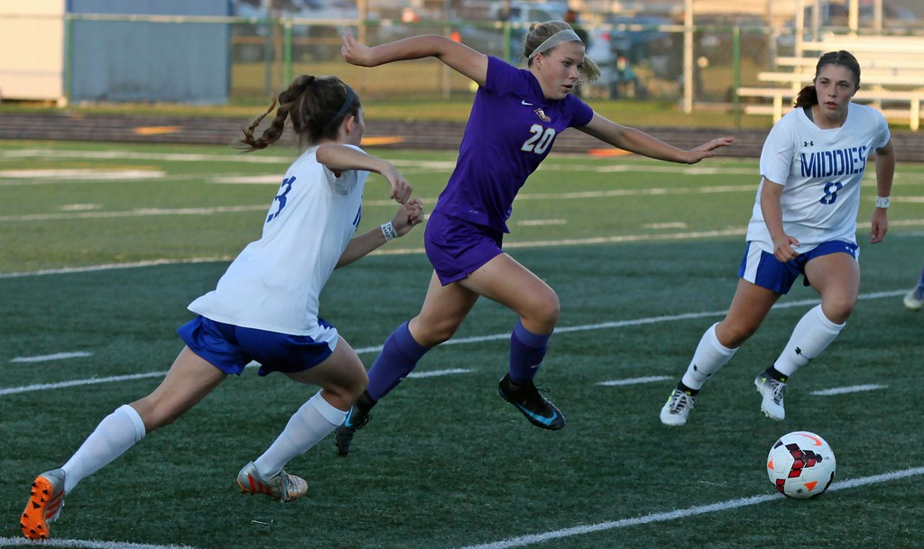 . Randy Meyers - The Morning Journal<br> Avon\'s Anna Brethauer kicks the ball between Stephanie Sturgeon and Alexia Hamm of Midview during the first half on Sept. 6.