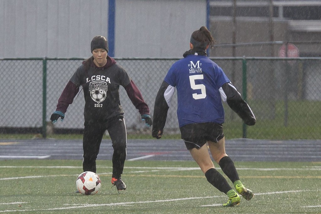 . Jen Forbus - The Morning Journal<br> Wellington\'s Emma Horoschak (Grey) has to pass Avon\'s Megan Sikora to move the ball down the field during the Lorain County Senior All-Star Game on Nov. 18.