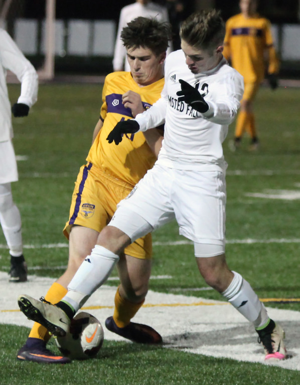 . Randy Meyers - The Morning Journal<br> Mark Ortiz of Olmsted Falls tries to kick the ball away from Zach Culp of Avon during the first half of the Division I Elyria District final on Oct. 28 at North Ridgeville.