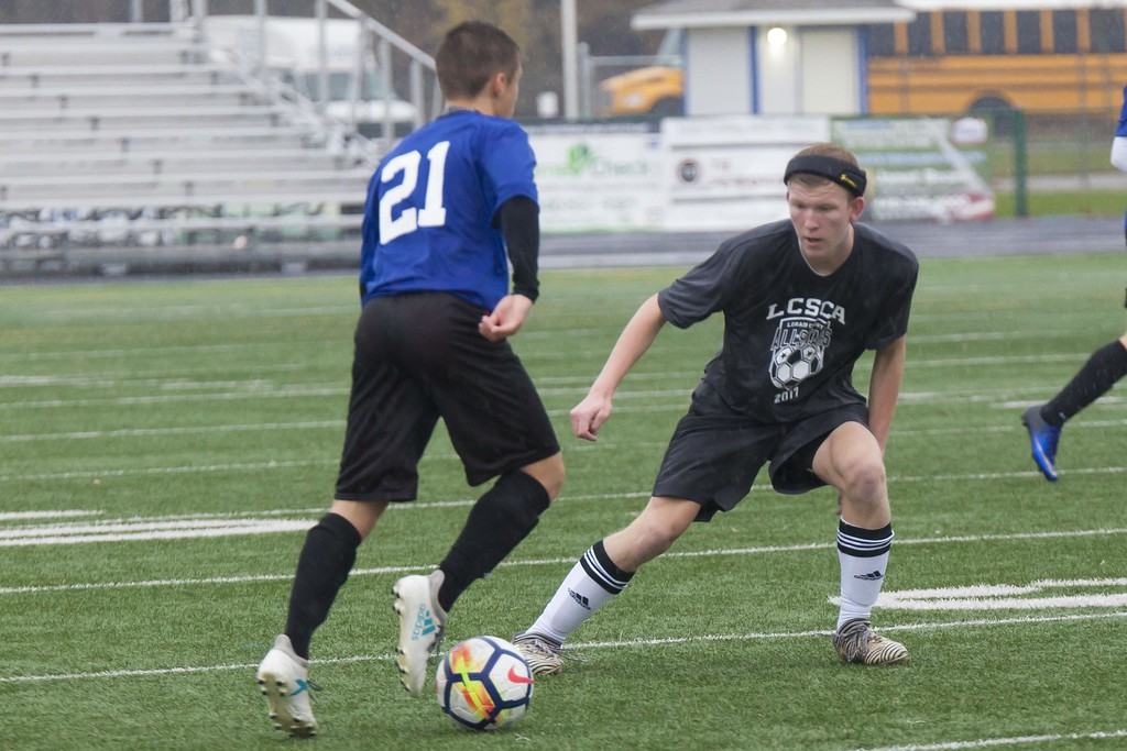 . Jen Forbus - The Morning Journal<br> Wellington\'s Cole McLean on the Blue team looks for a chance to pass Vermilion\'s Fielding Featherston on the Grey during the Lorain County Senior All-Star Game on Nov. 18.