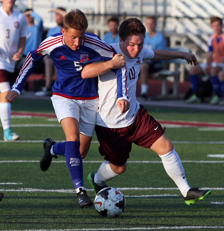 . Randy Meyers - The Morning Journal<br> Bay\'s Jack Graham and Bryan Kern of Rocky River are tangled together while going after the ball during the first half on Aug. 30.