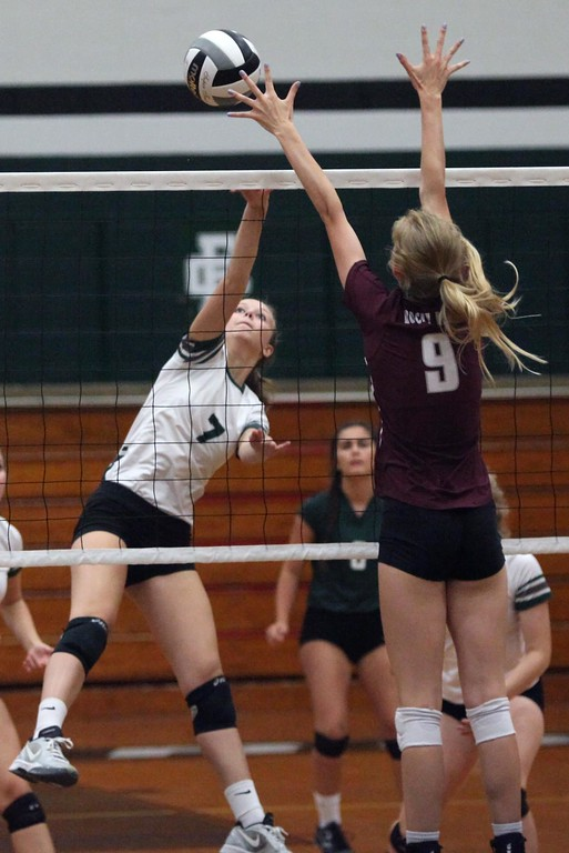 . Randy Meyers - The Morning Journal<br> Elyria Catholic\'s Haley Raible spikes the ball over Rachael Waite of Rocky River during the first set on Aug. 29.