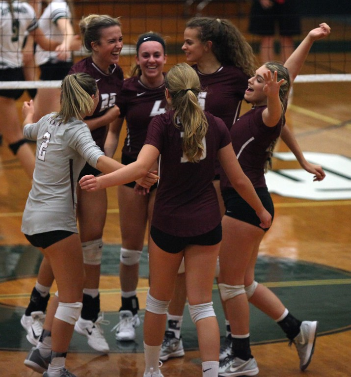 . Randy Meyers - The Morning Journal<br> Rocky River girls celebrate after winning the first set against Elyria Catholic on   Aug. 29.