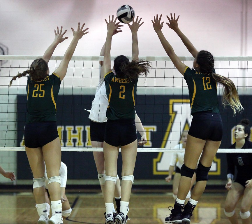 . Randy Meyers - The Morning Journal<br> Payton Jackson, Sarah Farley and Faith Rico of Amherst converge on the spike by Leah Schmidt of Westlake during the second set on Sept. 19.