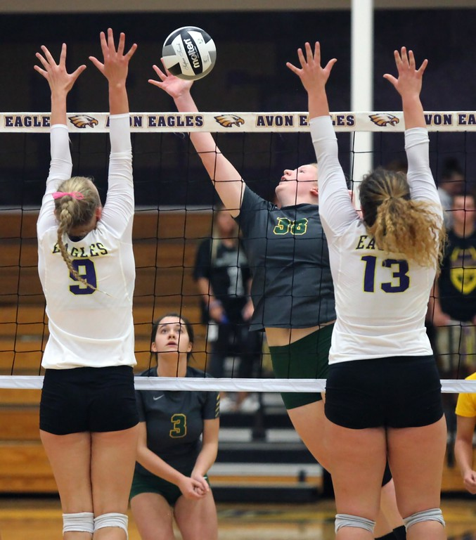 . Randy Meyers - The Morning Journal<br> Tory Small of Amherst taps the ball in between Gillian Romanchok and Emma Abfall of Avon during the first set on Nov. 14.
