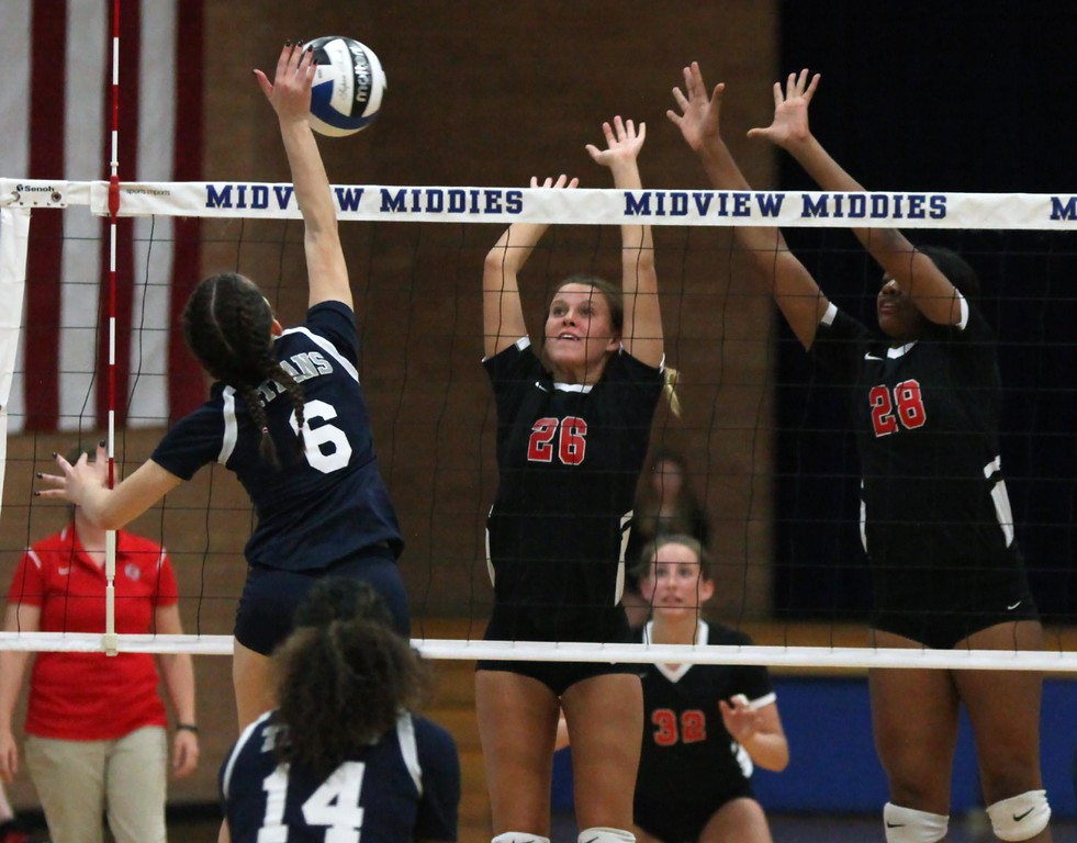 . Randy Meyers - The Morning Journal<br> Julia Velez of Lorain has her spike partially blocked by Emily Hyer of Elyria during the first set on Oct. 18.