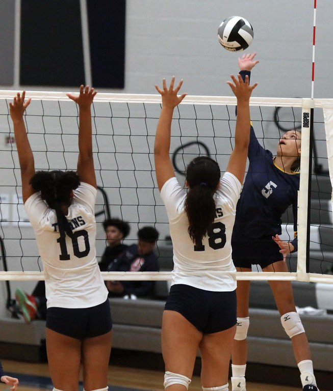 . Randy Meyers - The Morning Journal<br> North Ridgeville\'s Callista Wasuk spikes the ball over Lailah Carrion and Sydney Patterson of Lorain during the first set on Sept. 16.