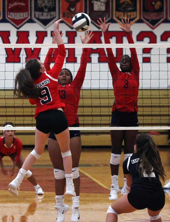 . Randy Meyers - The Morning Journal<br> Firelands Emily Squires spikes the ball over Tiffani Burke and Nya Grady-Norman of Oberlin for point on Aug. 31.