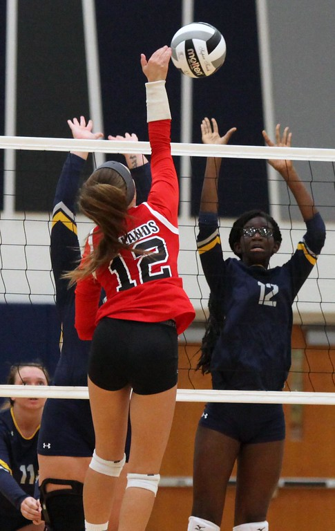 . Randy Meyers - The Morning Journal<br> Kristin DeWitt of Firelands spikes over Akua Agyemang and Kara Sullinger of North Ridgeville on Sept. 16.