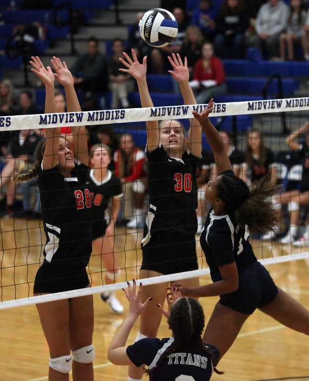 . Randy Meyers - The Morning Journal<br> Seven Townsel of Lorain has her tap partially blocked at the net by McKenna Keir and Emily Hyer of Elyria during the second set on Oct. 18.