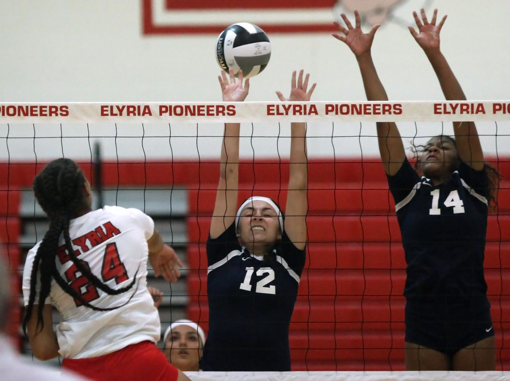 . Randy Meyers - The Morning Journal<br> Elyria\'s Alyssa White spikes the ball over Lorain\'s Maleigha Amador for point during the first set on Aug. 24.