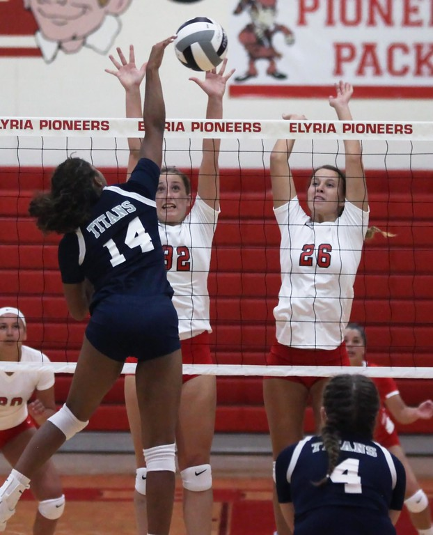 . Randy Meyers - The Morning Journal<br> Lorain\'s Seven Townsel taps the ball over for point against Elyria defenders Madi Smith and Emily Hyer on Aug. 24.