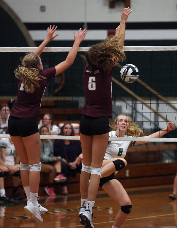 . Randy Meyers - The Morning Journal<br> Ava Rauser of Rocky River blocks the spike by Grace Shuckman of Elyria Catholic for point on Aug. 29.