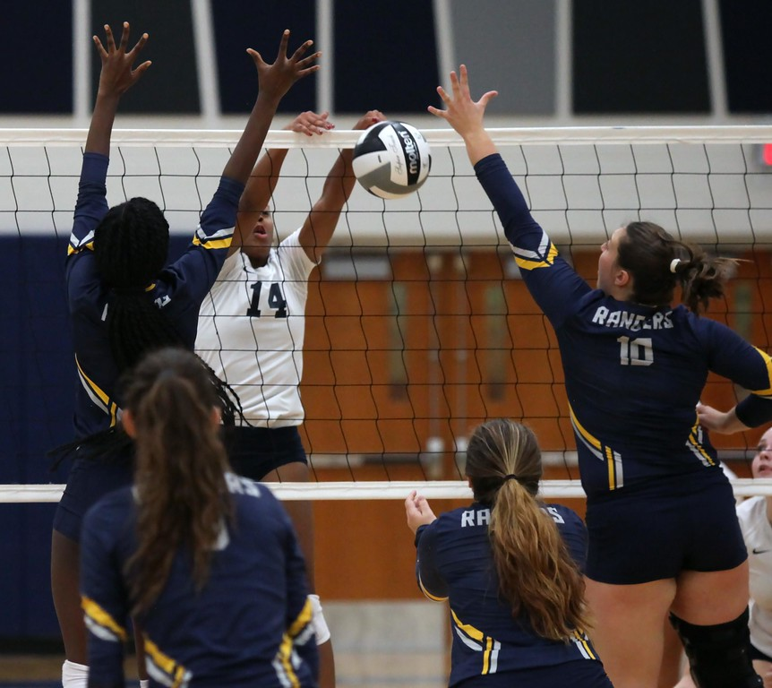 . Randy Meyers - The Morning Journal<br> Lorain\'s Seven Townsel spikes the ball in between Akua Agyemang amd Kara Sullinger of North Ridgeville on Sept. 16.