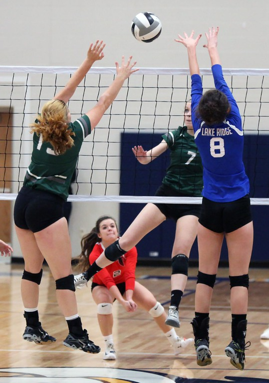 . Randy Meyers - The Morning Journal<br> Elyria Catholic\'s Haley Raible spikes the ball between her former teammate Meghan Allgretto and Isabel Bouzaher of Lake Ridge during the first match at the Lorain County Senior All-Star Game on Nov. 14.