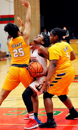 John P. Cleary |  The Herald Bulletin<br /> Anderson's Tyra Ford gets squeezed by Marion defenders Leilanu Jackson and Ayana Harvey as she drives the lane. Ford hit the shot she threw up while being fouled.