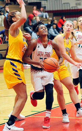 John P. Cleary |  The Herald Bulletin<br /> Anderson's Tyra Ford splits the Marion defenders as she drives to the basket.