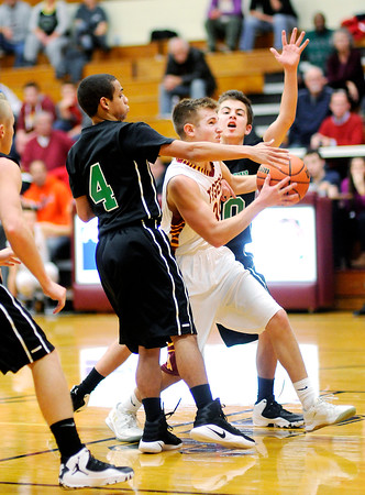 Don Knight | The Herald Bulletin<br /> Alexandria's Matthew Hensley drives through the defense of Yorktown's Jordan Edwards and Luke Avila into the lane at Alexandria on Tuesday.
