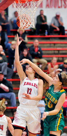 John P. Cleary |  The Herald Bulletin<br /> Frankton's Sydney Tucker get fouled across the face by Eastern's McKenzie Cooper as she goes to the basket.
