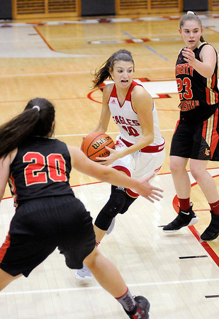 Don Knight | The Herald Bulletin<br /> Frankton's Addie Gardner splits a pair of Liberty Christian defenders, Elena Tufts (20) and Mady Rees (23), on a drive to the basket as the Eagles hosted the Lions on Thursday.