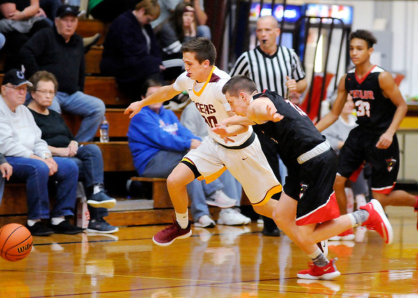 Don Knight | The Herald Bulletin<br /> Taylor's Clay Brubaker fouls Alexandria's Sam Hensley as they chase after a loose ball on Tuesday.