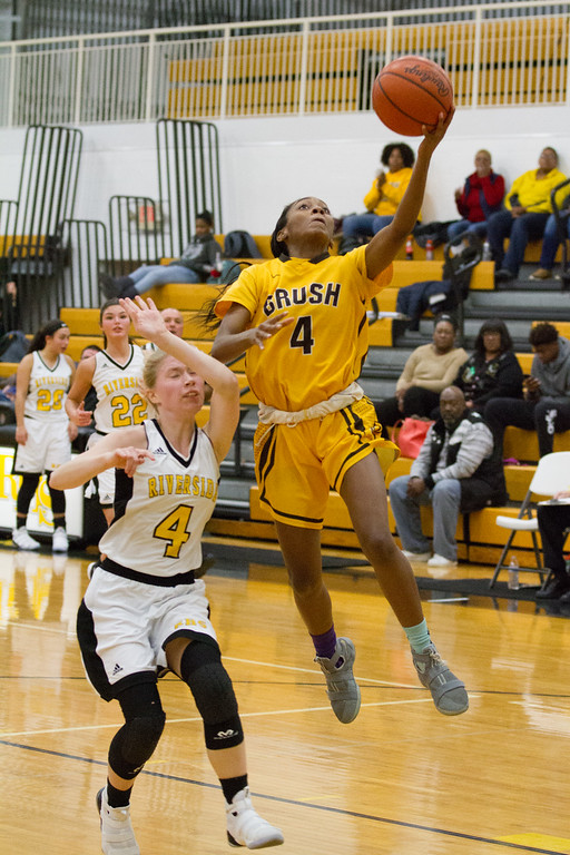 . Barry Booher - The News-Herald Brush\'s Danajah Sanders draws a foul from Eliza Parsons on her layup.