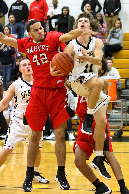 . Barry Booher - The News-Herald Andrew Keller drives and is fouled by Harvey\'s Marc Berry. Keller made both foul shots with 3.7 seconds left to give Riverside the lead 58-57. Harvey failed to get off a shot at the end.