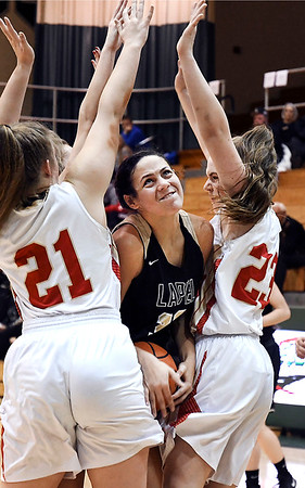 John P. Cleary | The Herald Bulletin<br /> Lapel's Makynlee Taylor tries to squeeze herself between Liberty Christian's Paige Grant and Mady Rees as she drove to the basket.