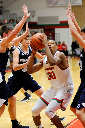 Don Knight | The Herald Bulletin<br /> Anderson's Tyquez Priester draws a trio of defenders as he shoots from the low post as the Indians hosted the Shenandoah Raiders on Friday.