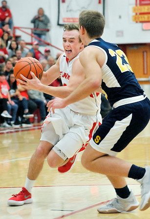 John P. Cleary    The Herald Bulletin<br /> Frankton's Travis McGuire tries to get a step on Shenandoah's Braydin Myers as he drives the lane.