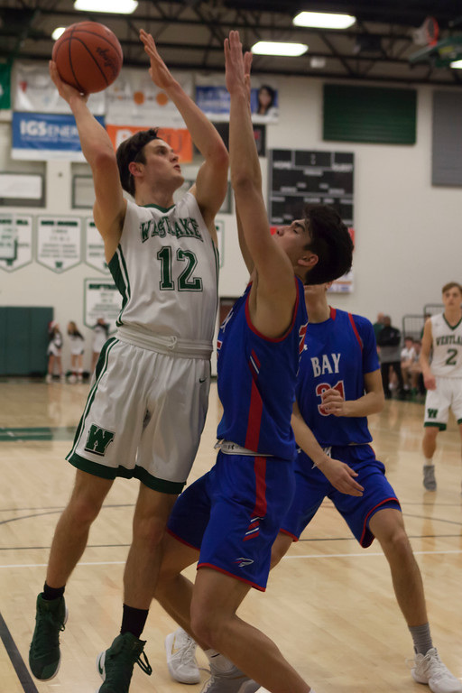 . Jen Forbus - The Morning Journal<br> Westlake\'s Neil McGrogan goes up for a shot against Bay\'s RJ Sunahara on Dec. 22.