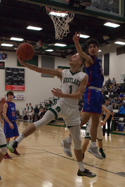 . Jen Forbus - The Morning Journal<br> Westlake guard Christian Kirallah gets a shot past Bay post RJ Sunahara by reversing under the basket on Dec. 22.