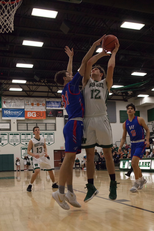 . Jen Forbus - The Morning Journal<br> Bay\'s Christian Dupps gets between the basket and Westlake\'s Neil McGrogan as McGrogan puts up a shot on Dec. 22.