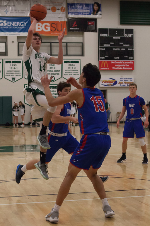 . Jen Forbus - The Morning Journal<br> Westlake\'s Anthony Rego elevates to shoot past Bay\'s RJ Sunahara on Dec. 22.