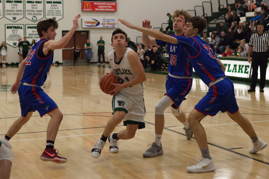 . Jen Forbus - The Morning Journal<br> Westlake\'s Tommy Lazevnick drives down the lane despite a trio of Rockets who intend to keep him out on Dec. 22.