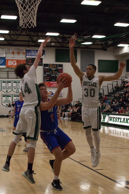 . Jen Forbus - The Morning Journal<br> Bay post Francis Sherman battles Westlake forward Anthony Rego (14) and guard Tim Waite (30) for a shot at the net on Dec. 22.