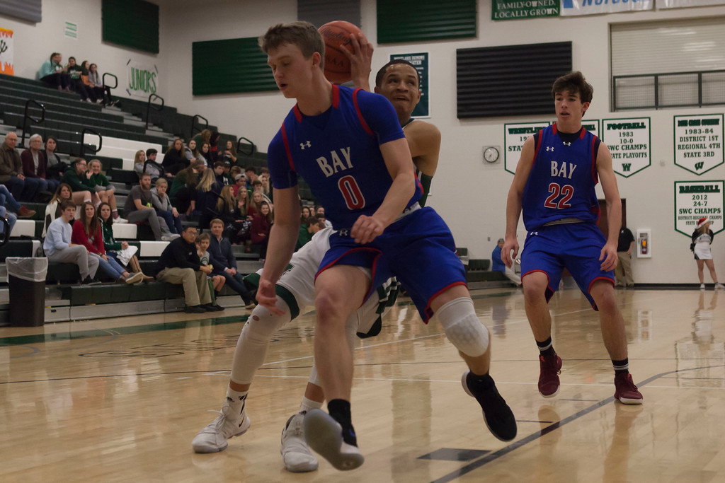 . Jen Forbus - The Morning Journal<br> A quick fake allows Westlake\'s Tim Waite to get by Bay\'s Erik Painter (0) on his way to the basket on Dec. 22.