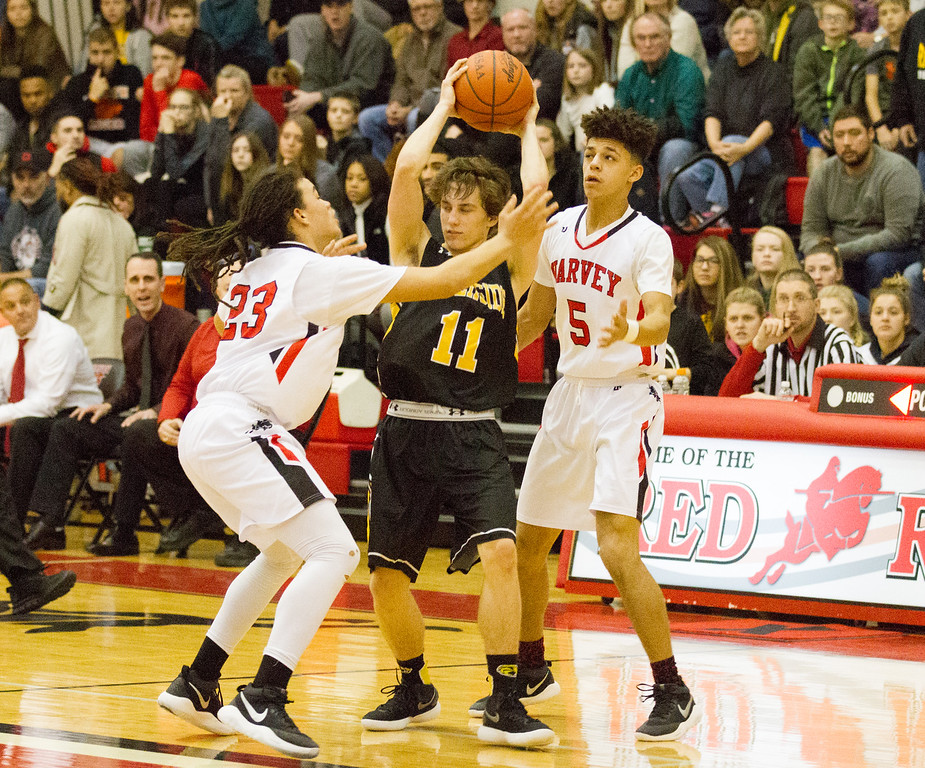 . Barry Booher - The News-Herald Harvey\'s Bishop Thomas (23) and Devon Holbert (5) pressure Riverside\'s Andrew Keller on Dec. 23