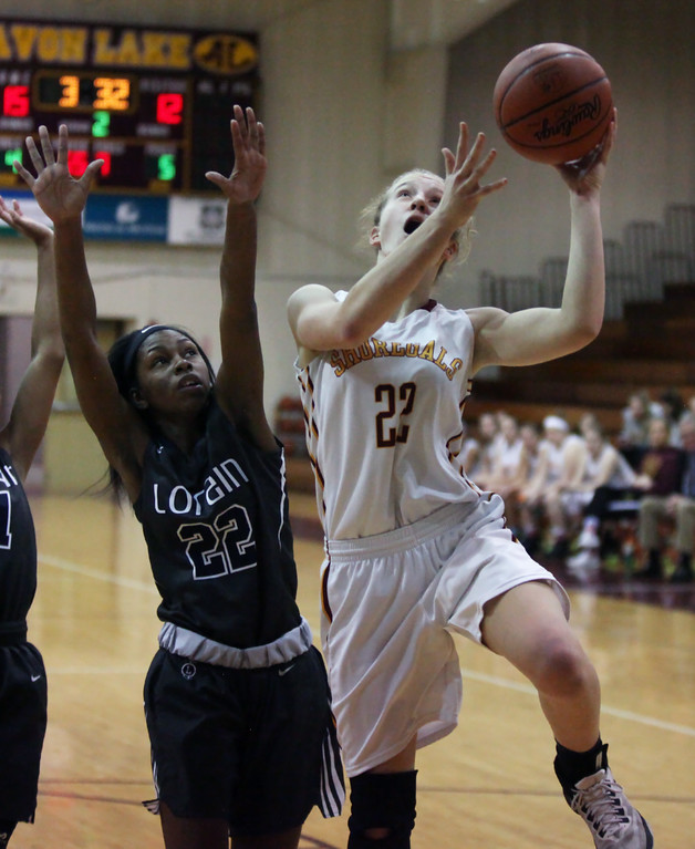 . Randy Meyers - The Morning Journal<br> Avon Lake\'s Grace Dean drives past Tanya Llanos of Lorain and scores during the second quarter on Dec. 23.