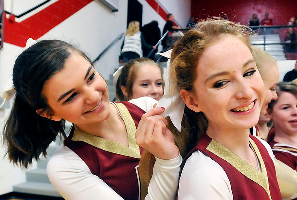John P. Cleary |  The Herald Bulletin<br /> Alexandria cheerleader Kylie Carney helps her teammate Kylie Carter with her hair bow as they prepared to cheer on their Tigers against Wapahani Wednesday evening at Selma.