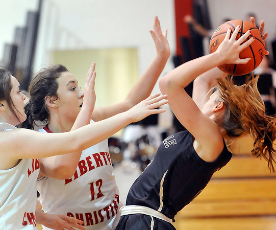 John P. Cleary    The Herald Bulletin<br /> Daleville's Jenny Shellabarger, with ball, gets pressured by Liberty Christian's Kennedy Fillmore and Sarah Aikin after stealing the ball from Aikins.