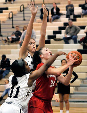 John P. Cleary |  The Herald Bulletin<br /> Frankton's Destyne Knight looks to go to the basket after a rebound as Lapel's Morgan Knepp and Breanna Boles defend her.