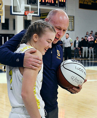 Shenandoah basketball coach Dameon Wyatt gives Kathryn Perry a big hug as he presents her with a basketball honoring her scoring 1,000 points.