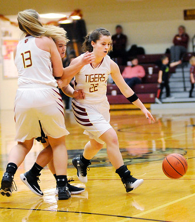 Don Knight | The Herald Bulletin<br /> Alexandria's Mackenzie McCarty (13) sets a screen giving Blaine Kelly an open look at the rim from behind the three-point arc as the Tigers hosted Madison-Grant on Thursday.