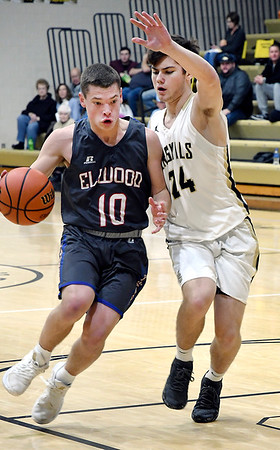 John P. Cleary   The Herald Bulletin<br /> Elwood's Seth Mireles gets a step on Madison-Grant's Lance Wilson as he drives the lane.