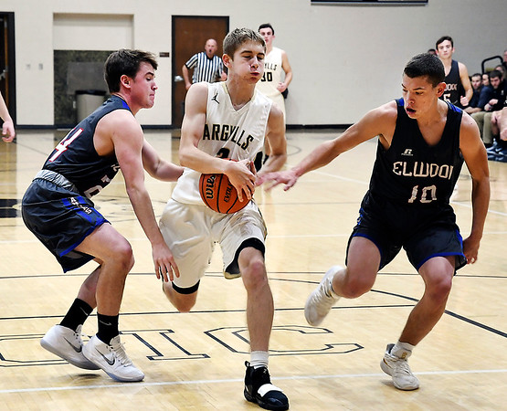 John P. Cleary   The Herald Bulletin<br /> Madison-Grant's Grant Brown looses control of the ball as he drives the lane against Elwood's Cole Courtney and Seth Mireles.