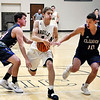 John P. Cleary | The Herald Bulletin<br /> Madison-Grant's Grant Brown looses control of the ball as he drives the lane against Elwood's Cole Courtney and Seth Mireles.